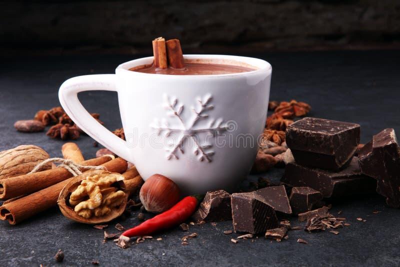 Filiżanka gorąca czekolada, cynamonowi kije, dokrętki i czekolada na dar, obrazy stock