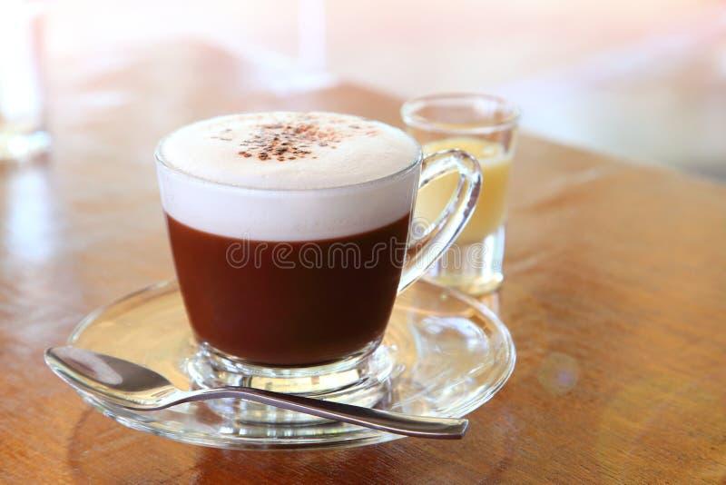 Filiżanka gorąca czekolada z pianą na wierzchołku i strzał słodzący zgęszczony mleko na drewnianym stole w kawiarni obraz royalty free