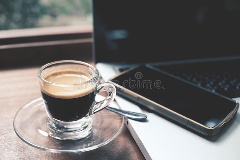 Filiżanka gorąca kawy espresso kawa z laptopem i smartphone fotografia stock