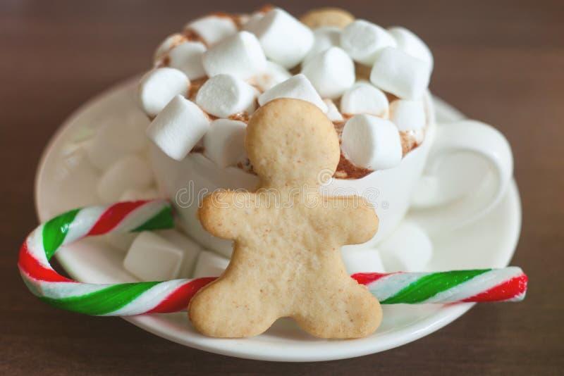 Filiżanka gorący kakao z śmietanką, marshmallows, imbirowy chlebowy mężczyzna, cukierek trzciny kij na drewnianym stole dla bożyc zdjęcia stock