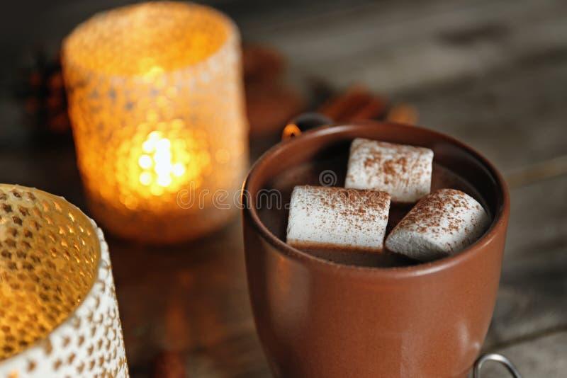 Filiżanka gorący kakao z marshmallows i świeczkami na stole, zbliżenie zdjęcia royalty free