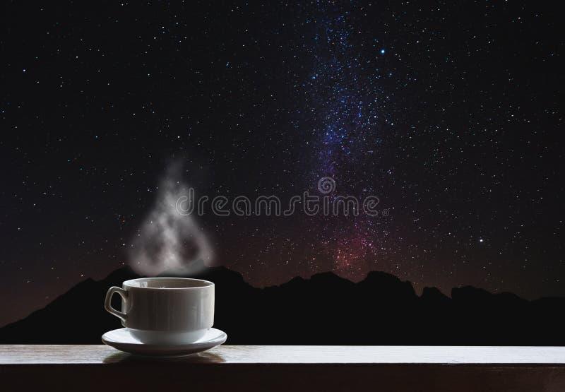 Filiżanka gorący napoje na stole z pięknym Milky sposobem z sylwetki halną przejażdżką Milky sposób zwiedza przy nocą zdjęcia royalty free