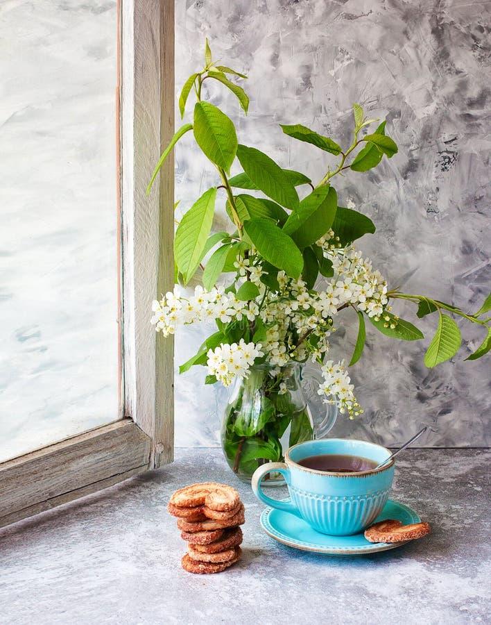 Filiżanka herbata, ciastka, ptasiej wiśni bukiet w szklanej wazie na szarość stole Berlińscy ciastka Wiosna target534_0_ drewnian obraz royalty free