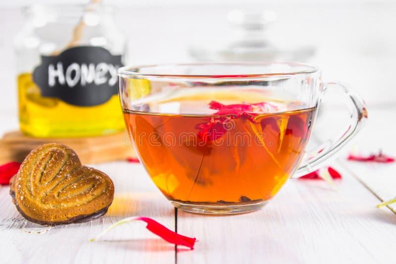 Filiżanka herbata, ciastka, w tle puszka miód i garnek czarna ziołowa kwiecista herbata na białym drewnianym stole fotografia stock