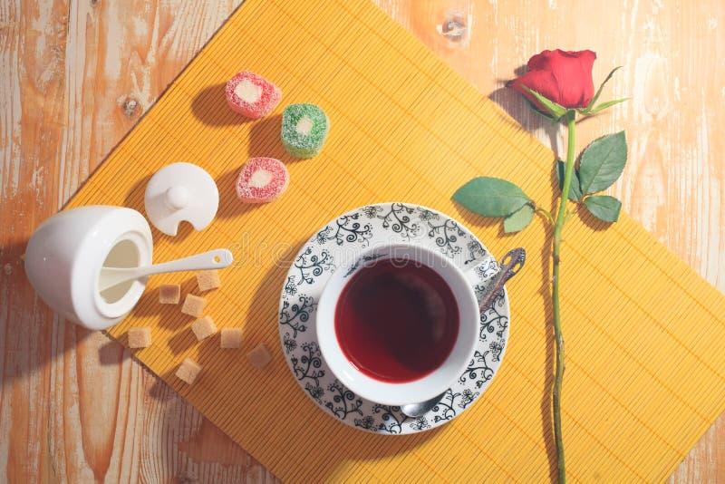 Filiżanka herbata, cukierki i czerwieni róża, obraz stock
