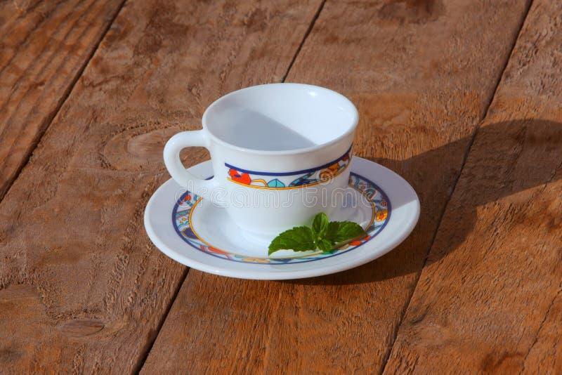 Filiżanka herbata i mennica na drewnianym tle fotografia royalty free