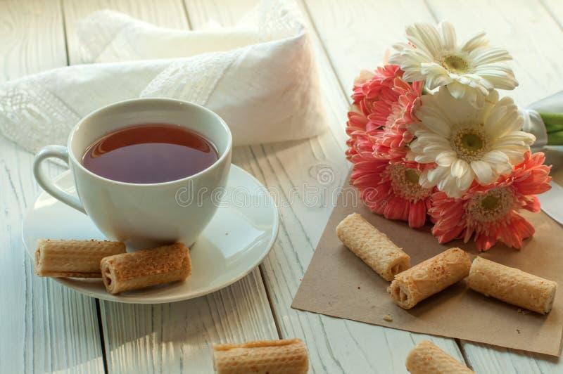 Filiżanka herbata, kilka ciastka, koronkowa pielucha i bukiet wiosna, kwitnie na białej drewnianej powierzchni fotografia royalty free