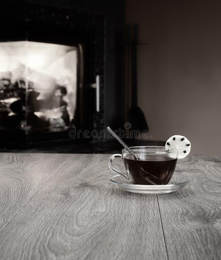 Filiżanka herbata na stole przeciw tłu ogień w grabie zdjęcia stock
