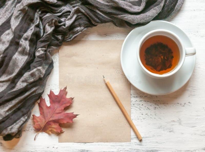 Filiżanka herbata na stole z pasiastą ciepłą etola, szalikiem i prześcieradło papier dla lub notatek, nakreślenia lub ołówek zdjęcie stock