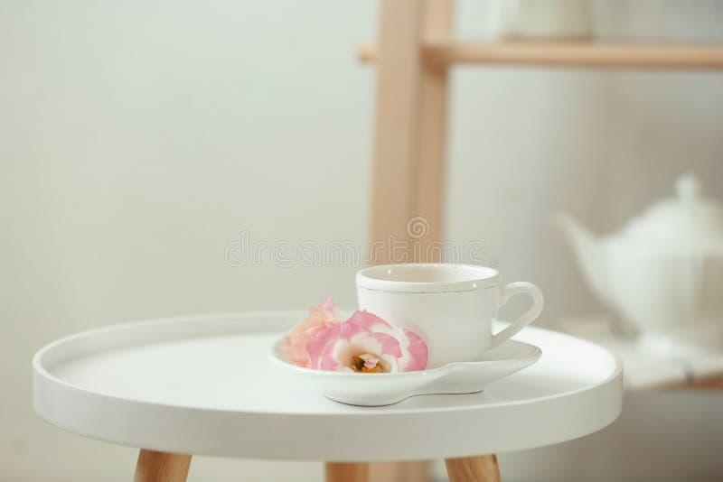 Filiżanka herbata, spodeczek i kwiaty na stole, obraz royalty free