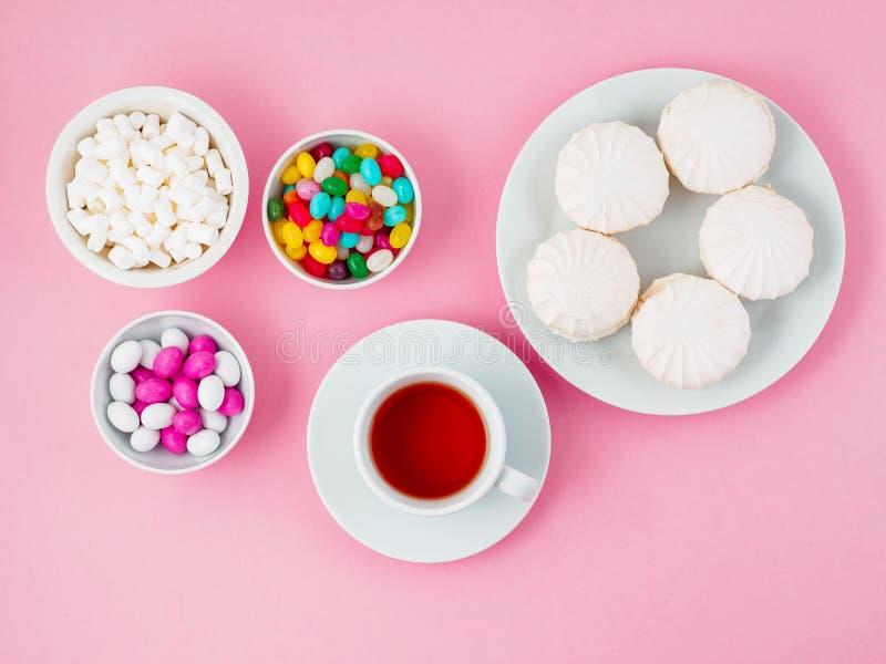 Filiżanka herbata, talerze różni marshmallows, lizaki, obrazy royalty free