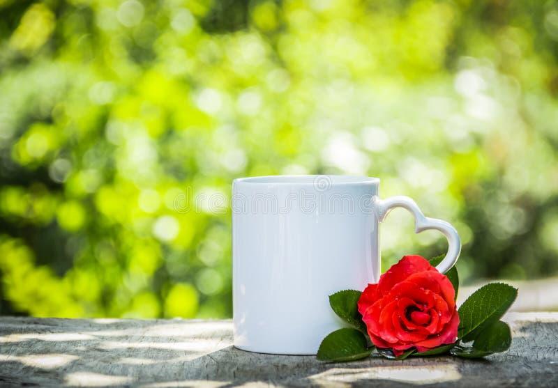 Filiżanka herbata w pogodnym zieleń ogródzie Kubek z serca i czerwieni różą obrazy royalty free