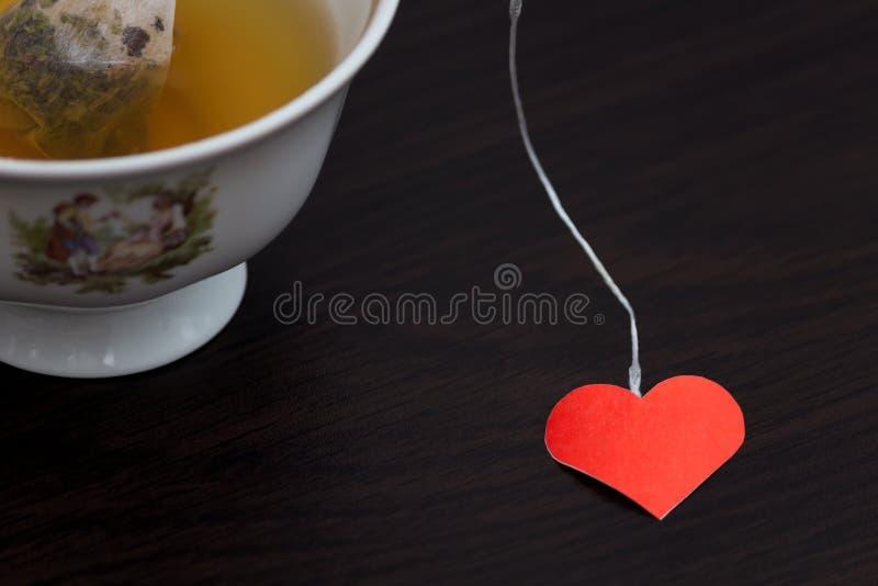 Filiżanka herbata z kierowym kształtem na czarnym drewnianym stole obrazy royalty free