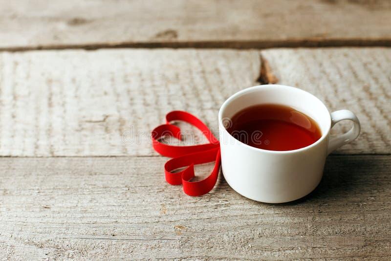 Filiżanka herbata z kierowym kształtem na rocznika drewnianym stole, minimalny pojęcie valentine macierzystego dnia ranku śniadan fotografia royalty free