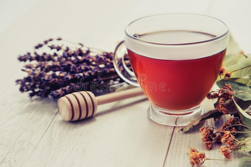 Filiżanka herbata z miodową chochlą i kwiatami na rocznika drewnianym tle lawendowymi i lipowymi zdjęcie stock
