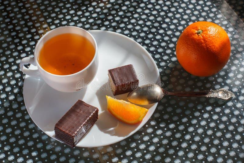 Filiżanka herbata z opłatkami w czekoladzie z ciastkami i pomarańcze obrazy stock