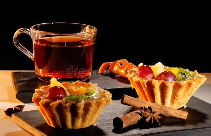 Filiżanka herbata z tortem, cynamonem i anyżem na tacy, obrazy stock