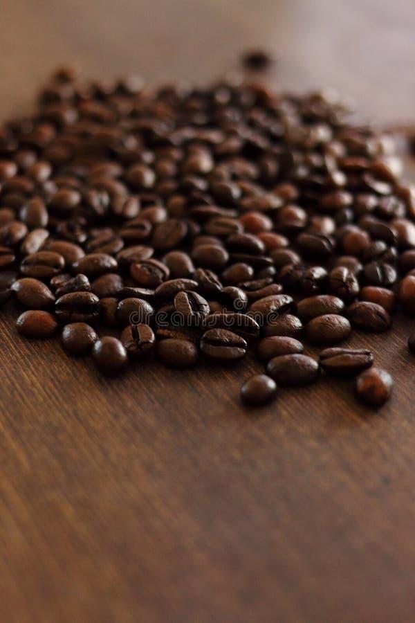 Filiżanka i kawowe fasole na ciemnym drewnie obrazy royalty free