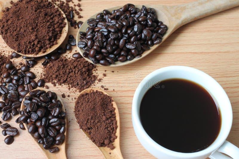 Filiżanka i kawowe fasole na drewno stole fotografia stock