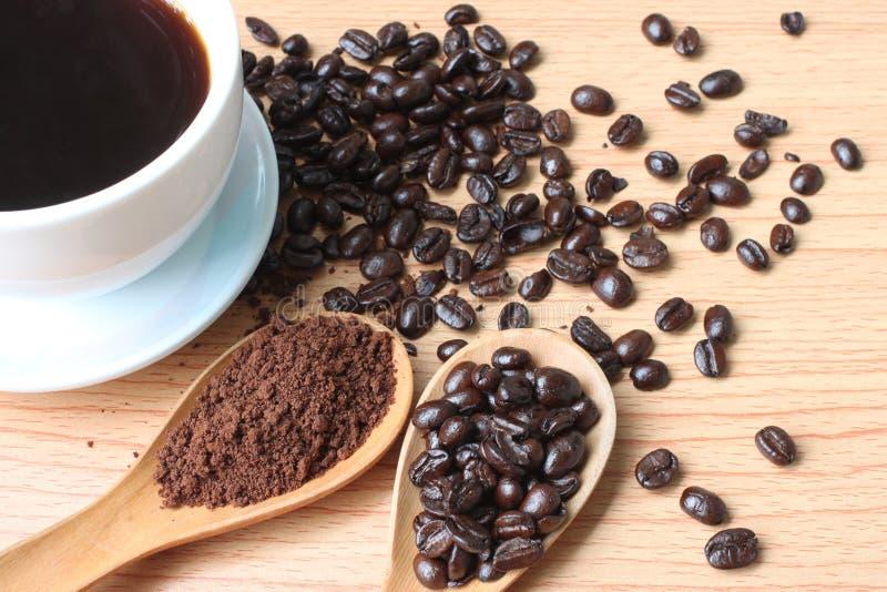 Filiżanka i kawowe fasole na drewno stole zdjęcie stock