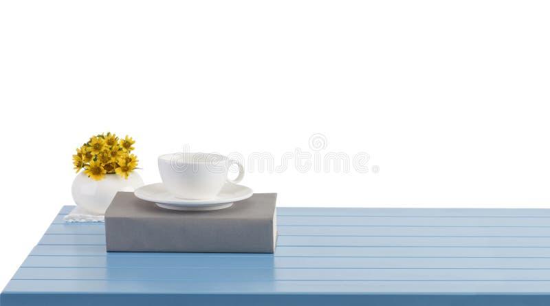 filiżanka i książka na błękitnym drewnianym stole obrazy stock
