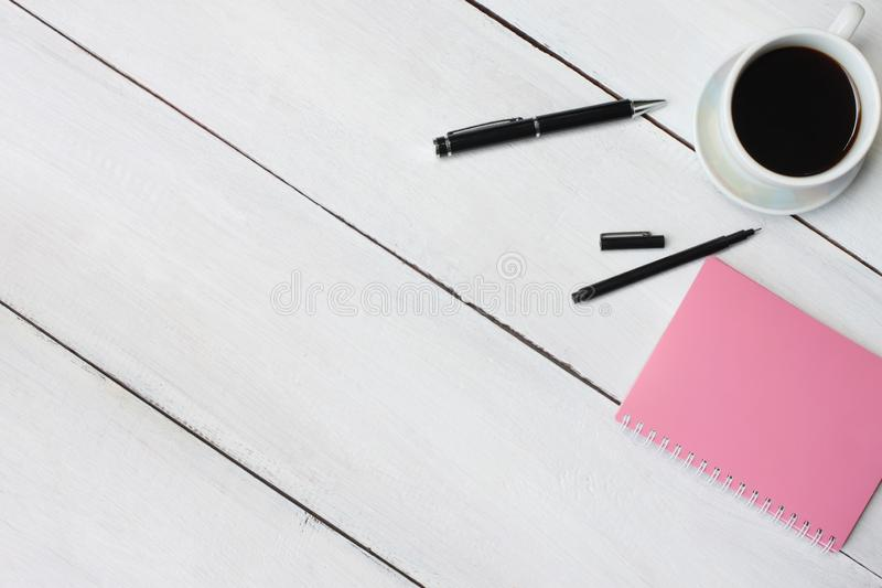 Filiżanka i pióro, notatnik na białym drewnianym biurku i odbitkowego s obrazy stock