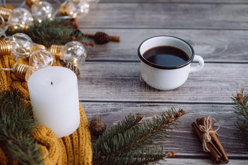 Filiżanka kawy, świeczka, garbki, cynamon, świerczyn gałąź i ciepły pomarańczowy szalik, i dekorujący z dowodzonymi światłami na  fotografia stock
