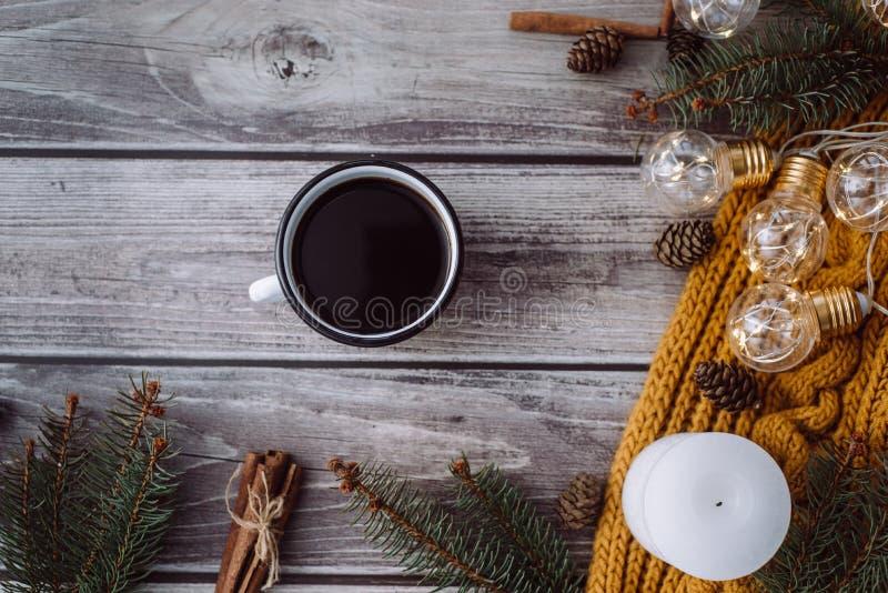 Filiżanka kawy, świeczka, garbki, cynamon, świerczyn gałąź i ciepły pomarańczowy szalik, i dekorujący z dowodzonymi światłami na  zdjęcie stock