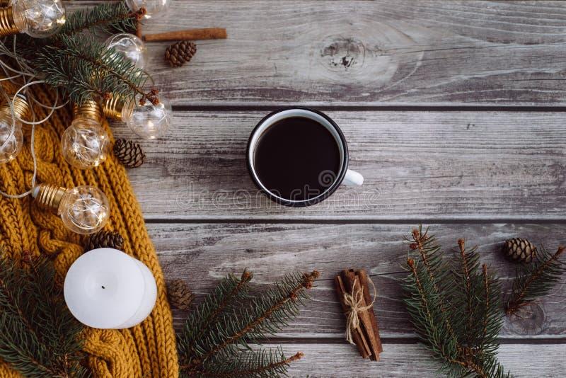 Filiżanka kawy, świeczka, garbki, cynamon, świerczyn gałąź i ciepły pomarańczowy szalik, i dekorujący z dowodzonymi światłami na  obrazy stock