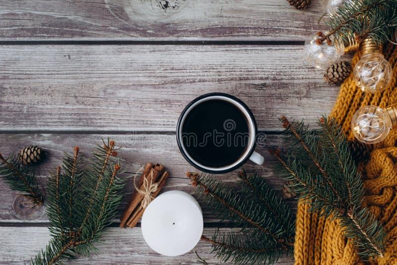 Filiżanka kawy, świeczka, garbki, cynamon, świerczyn gałąź i ciepły pomarańczowy szalik, i dekorujący z dowodzonymi światłami na  fotografia royalty free