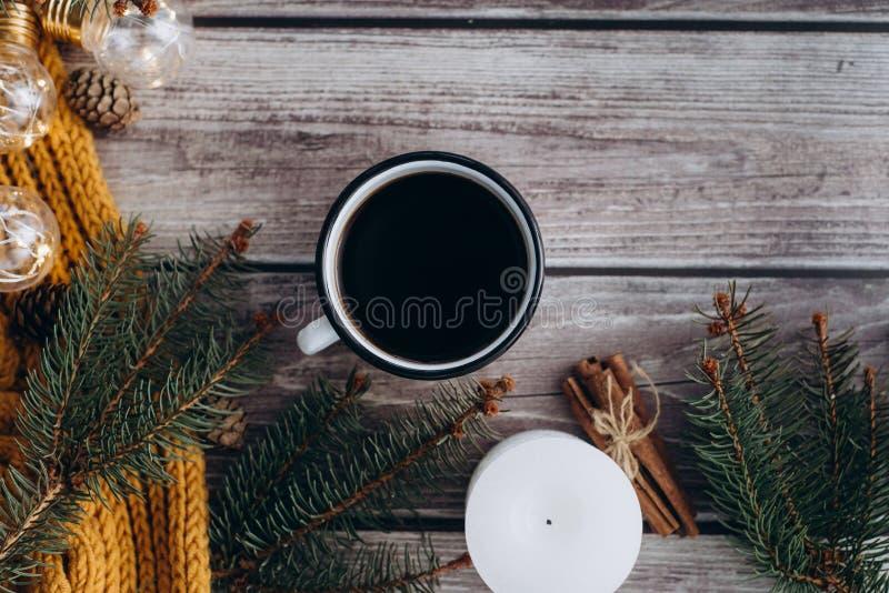 Filiżanka kawy, świeczka, garbki, cynamon, świerczyn gałąź i ciepły pomarańczowy szalik, i dekorujący z dowodzonymi światłami na  zdjęcia stock