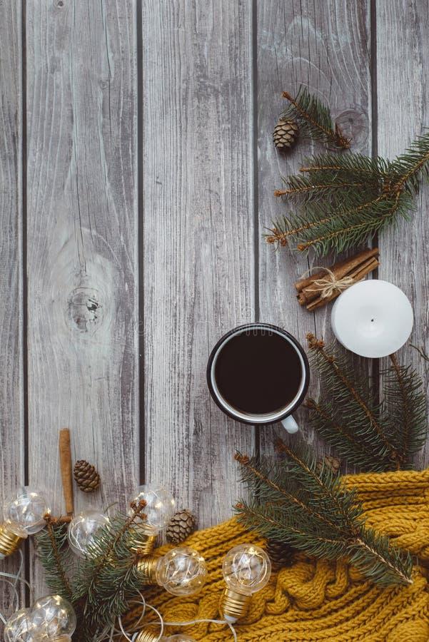 Filiżanka kawy, świeczka, garbki, cynamon, świerczyn gałąź i ciepły pomarańczowy szalik, i dekorujący z dowodzonymi światłami na  obrazy royalty free