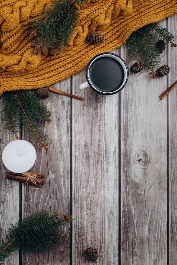 Filiżanka kawy, świeczka, garbki, cynamon, świerczyn gałąź i ciepły pomarańczowy szalik na drewnianym stole, obraz stock
