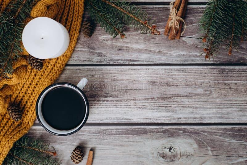Filiżanka kawy, świeczka, garbki, cynamon, świerczyn gałąź i ciepły pomarańczowy szalik na drewnianym stole, zdjęcia stock