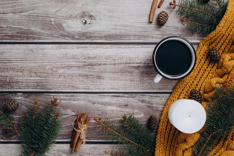 Filiżanka kawy, świeczka, garbki, cynamon, świerczyn gałąź i ciepły pomarańczowy szalik na drewnianym stole, fotografia stock