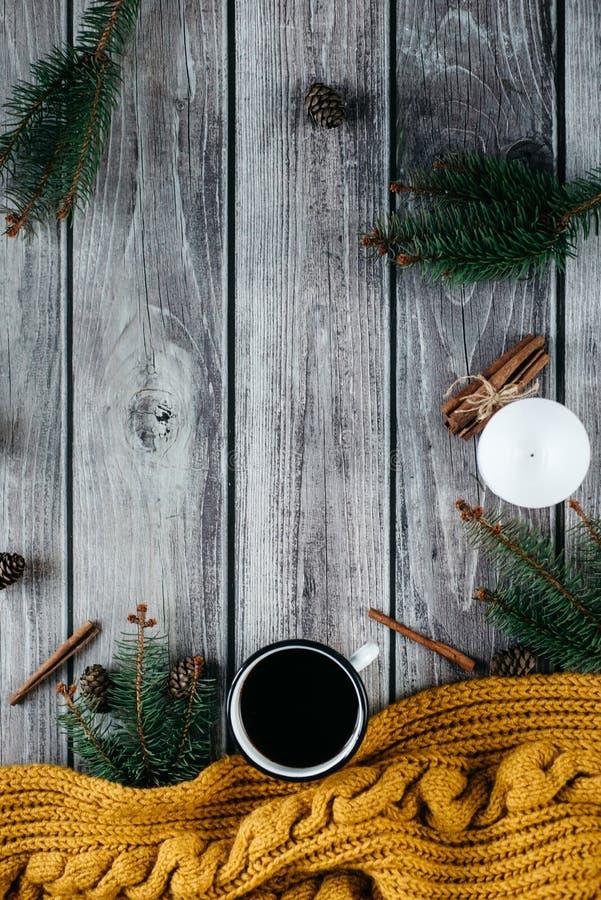 Filiżanka kawy, świeczka, garbki, cynamon, świerczyn gałąź i ciepły pomarańczowy szalik na drewnianym stole, obraz royalty free