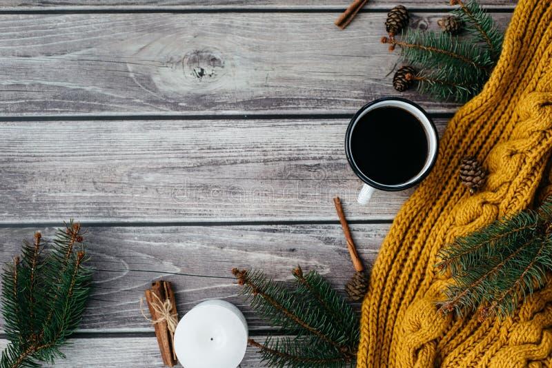 Filiżanka kawy, świeczka, garbki, cynamon, świerczyn gałąź i ciepły pomarańczowy szalik na drewnianym stole, fotografia royalty free