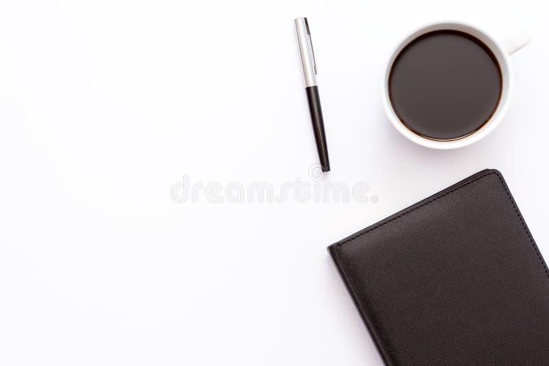 Filiżanka kawy, czarny dzienniczek i pióro na białym tle, Minimalny biznesowy pojęcie pracujący miejsce w biurze zdjęcie royalty free