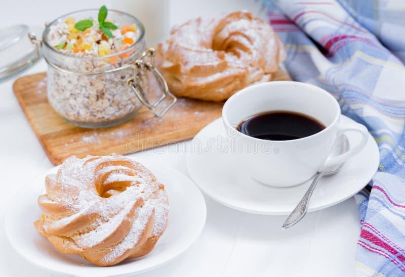 Filiżanka kawy, granola, babeczki na białym tle blisko pasiastej pieluchy fotografia royalty free