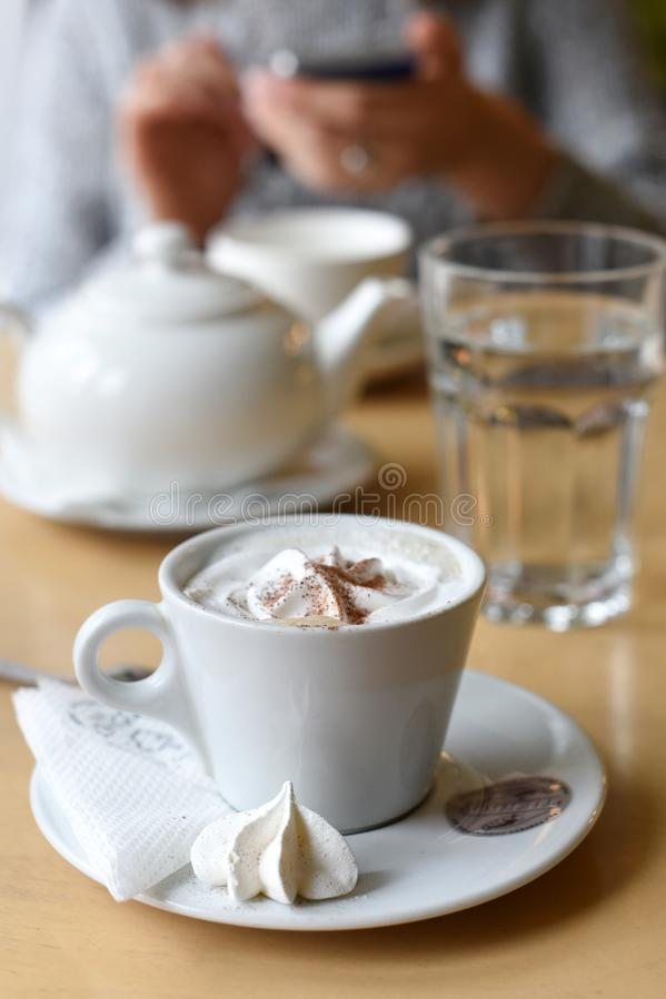 Filiżanka kawy, herbaciany garnek i para kobiety ` s ręki trzyma telefon komórkowego w tle, obraz royalty free
