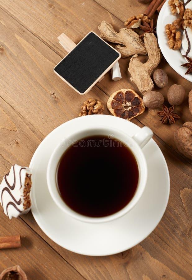 Filiżanka kawy i ciastka na drewnianym tle, pikantności i dekoraci, miniaturowa czerni deska dla teksta, odgórny widok, retro sty fotografia stock