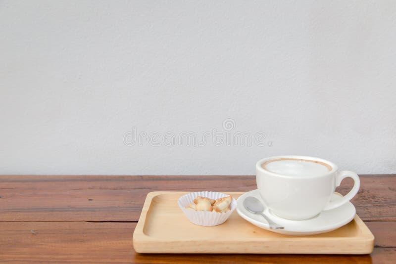 Filiżanka kawy i ciastko na drewno stole obrazy stock