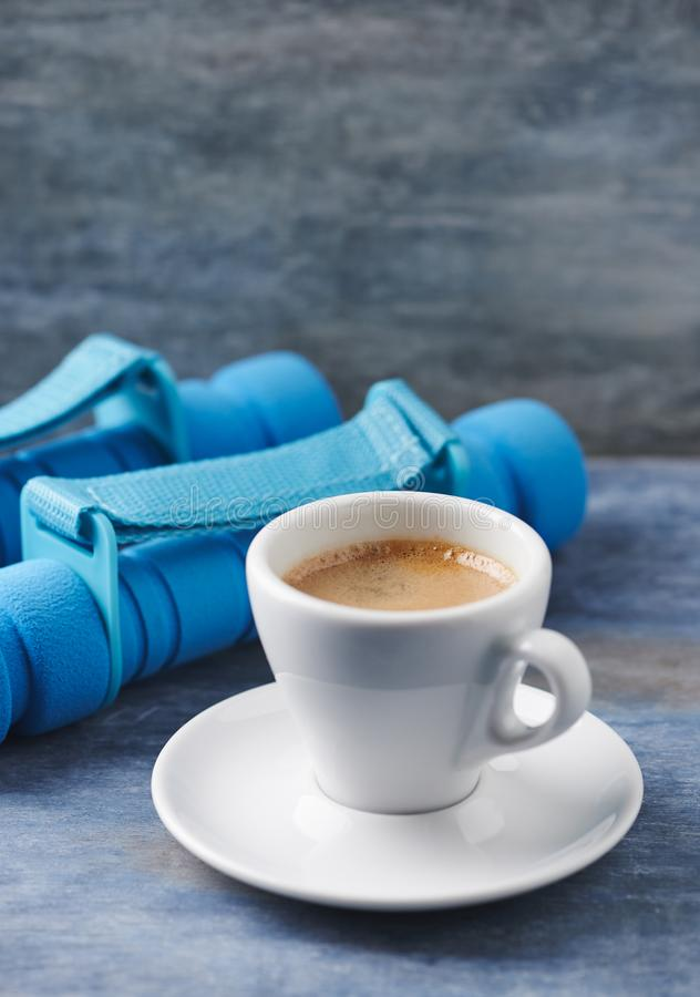 Filiżanka kawy i dumbbells na błękitnym drewnianym tle zdjęcia royalty free