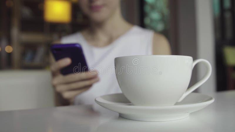 Filiżanka kawy i kobieta z smartphone na tle zdjęcie royalty free