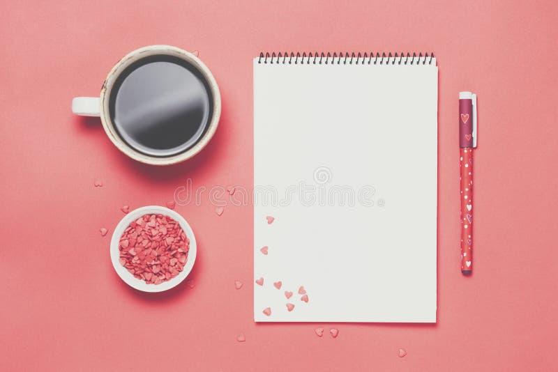 Filiżanka kawy i notatnik na czerwonym tle Minimalistic styl Odgórny widok, mieszkanie nieatutowy zdjęcia stock