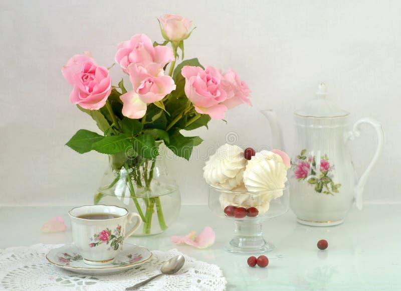 Filiżanka kawy, kawowy garnek, marshmallow w szklanym pucharze i bukiet różowe róże na stole, 1 życie wciąż Zgłasza położenie zdjęcie royalty free