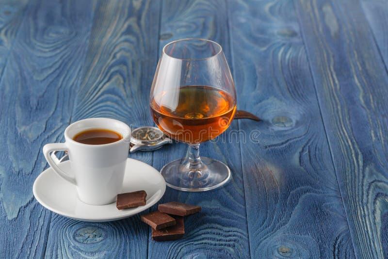 Filiżanka kawy, koniaka szkło i czekolada na drewnianym stole, fotografia stock