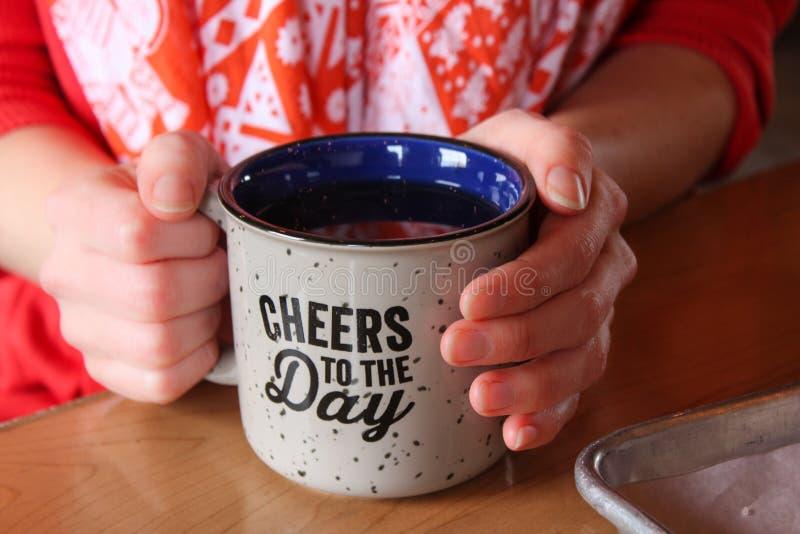 Filiżanka kawy lub herbata trzymający dwa rękami przy stołem zdjęcia stock