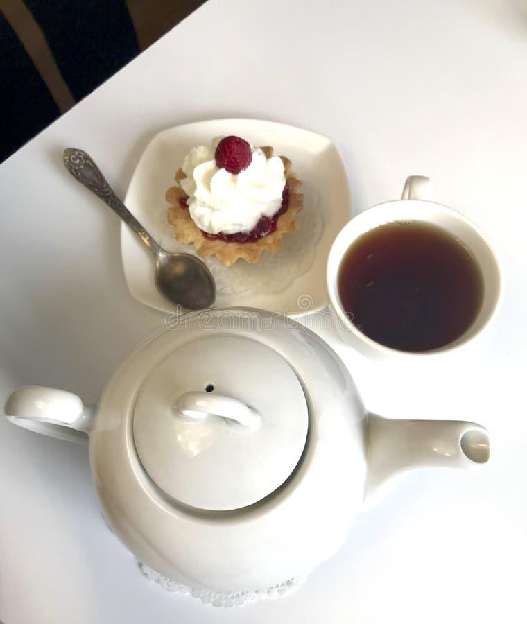 Filiżanka kawy, malinowe jagody i torty jest na stole zdjęcie stock