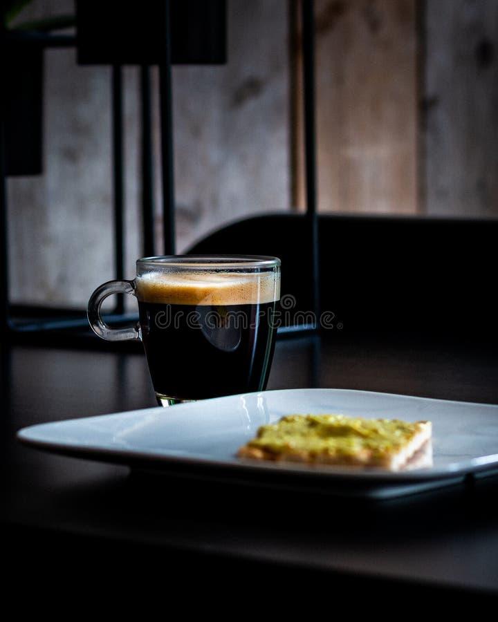 Filiżanka kawy na czarnym stole z krakersem na talerzu dla śniadania obraz royalty free